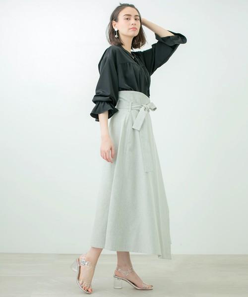 黒のキャンディスリーブのスキッパーブラウスにミントグリーンのスカートを合わせた女性