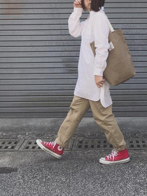 白いシャツにチノパンを合わせて赤いスニーカーを履いた女性