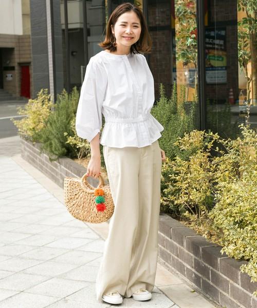 白フリルトップスにベージュパンツを履いた女性