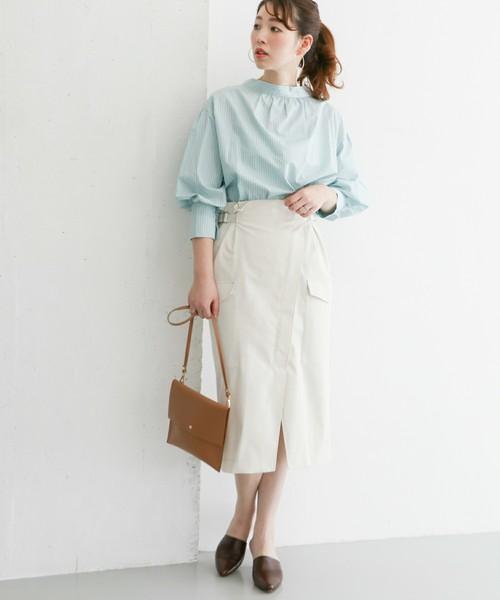 ライトブルーのブラウスに白のラップスカートを履いた女性