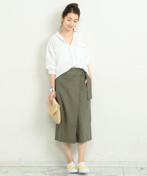 白のシャツにカーキのラップスカートを履いた女性