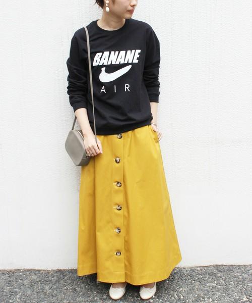 黒いロゴスウェットにイエロースカートを履いた女性