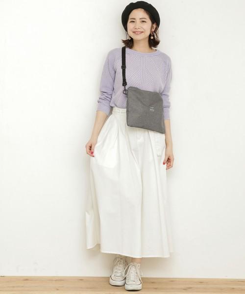 ラベンダー色のニットに白のフレアスカートを合わせて、グレーのサコッシュを肩に掛けた女性