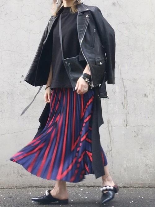 黒のトップスにストライプ柄のスカートを合わせて、レザーのサコッシュを斜め掛けしてライダースを羽織った女性