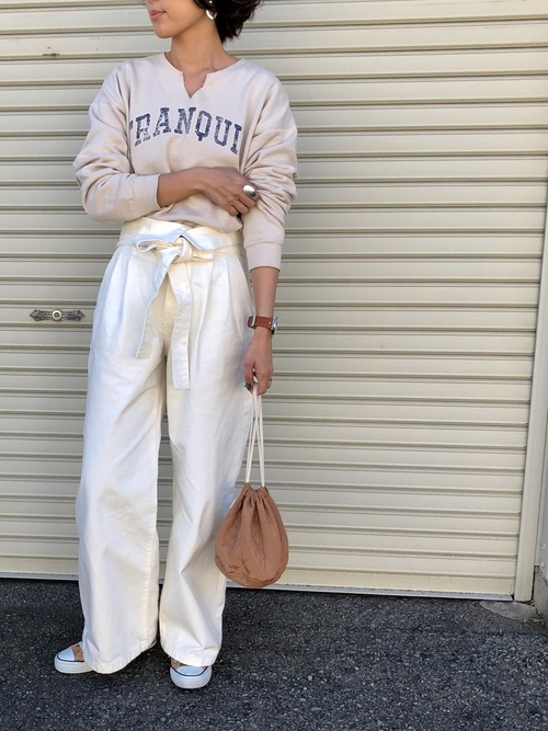 ベージュのスウェットに白のデニムパンツを合わせた女性