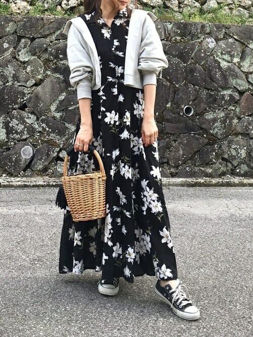 黒の花柄ワンピースにグレーのショート丈パーカーを羽織った女性