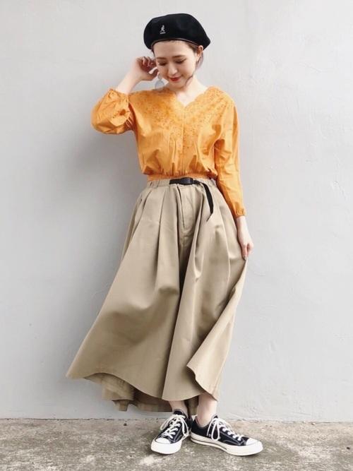 オレンジブラウスにベージュチノスカートのコーデ