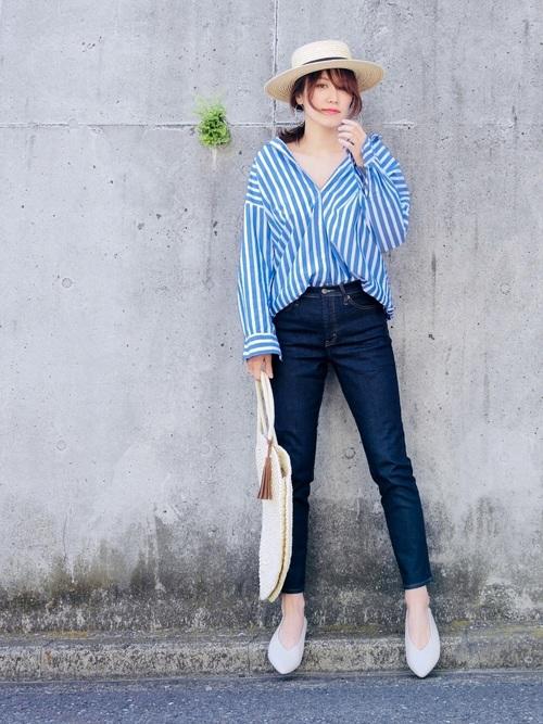 ストライプシャツのデニムパンツに麦わら帽子を被った女性
