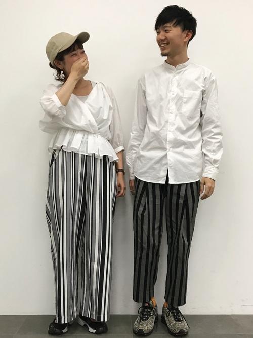 白のブラウスにストライプのパンツを合わせた女性と、白シャツにストライプのパンツを合わせた男性