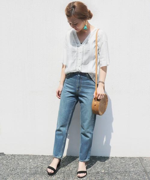 白ブラウスにデニムパンツを履いた女性