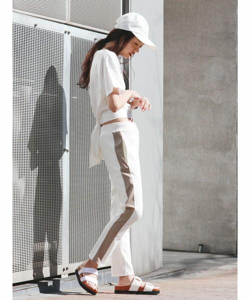 白トップスにラインパンツを履いた女性