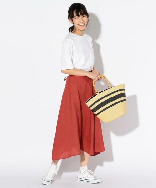白のカットソーに赤のスカートを履いた女性