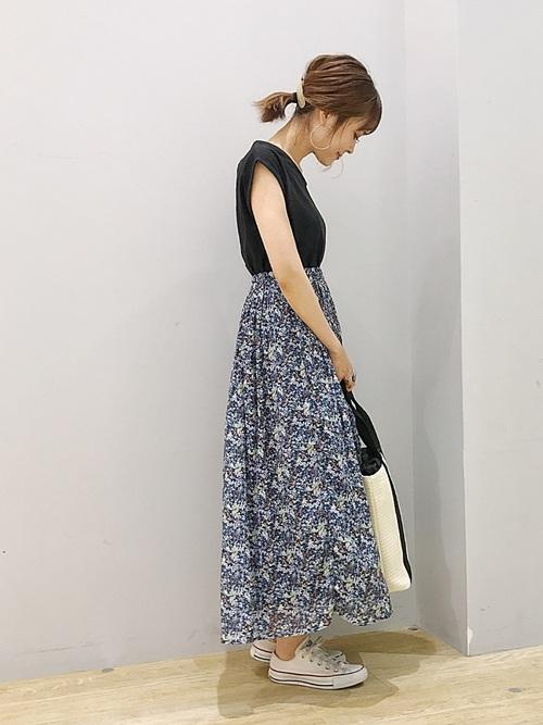 黒Tシャツに花柄スカートの女性