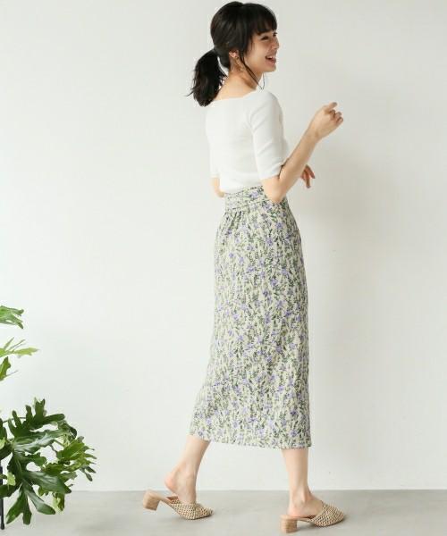 白トップスに花柄スカートを履いた女性
