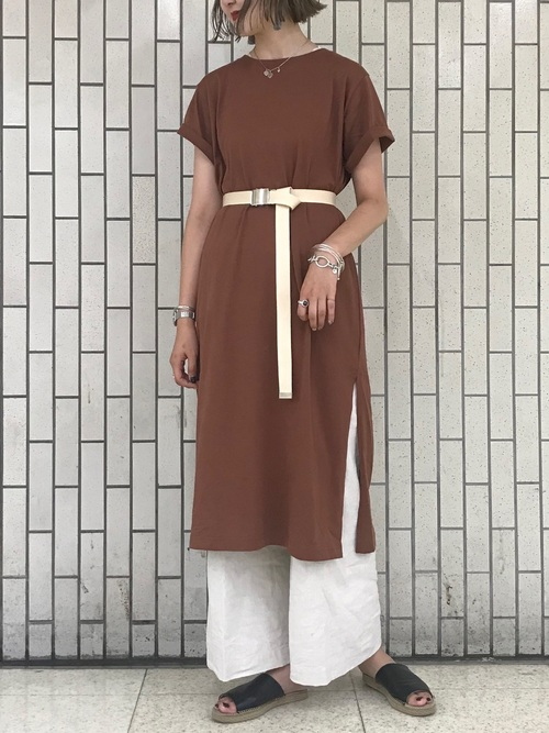 ブラウンのワンピースに白のワイドパンツを合わせて、白のガチャベルトをした女性