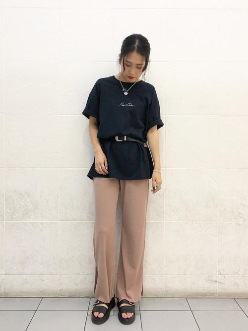 黒Tシャツにリブパンツを履いた女性