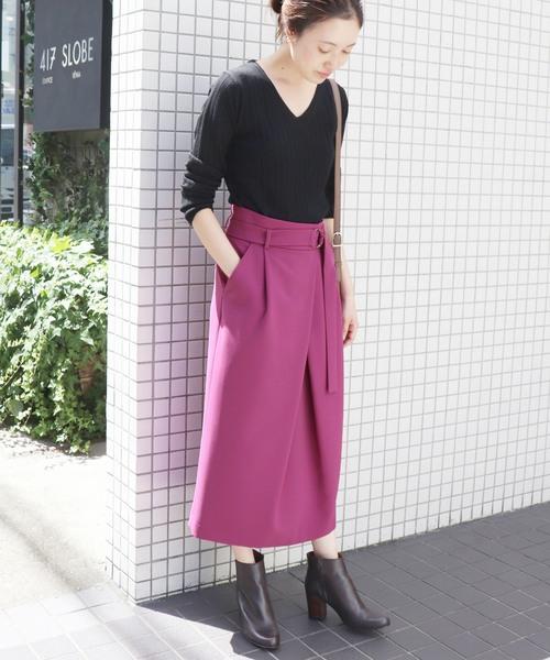 黒ニットにピンクスカートを履いた女性