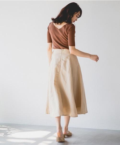 ブラウンの後ろ開きニットにベージュのスカートを合わせた女性
