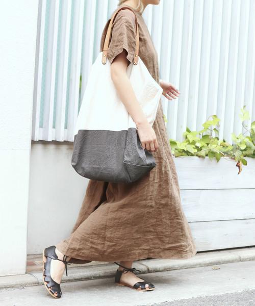 ベージュワンピースにデカバッグを持った女性