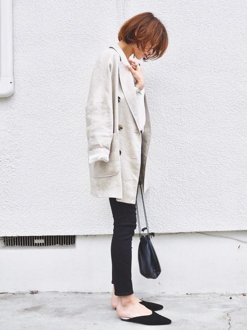 ベージュジャケットに黒スキニーパンツと似合う靴のバックオープンサンダルを合わせたレディース秋冬コーディネート