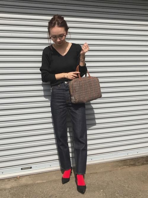 黒ニットにデニムパンツと赤靴下と黒パンプスの秋冬の大人女子会コーディネート