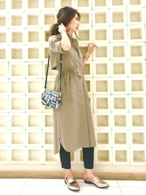 ベージュのシャツワンピに黒パンツを合わせて、メタリックゴールドのローファーを履いた女性