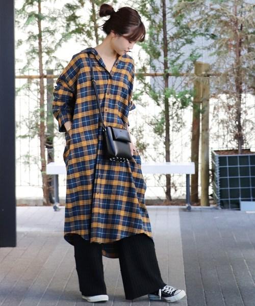 イエローとブルーのチェック柄のシャツワンピに黒のワイドパンツを合わせた女性