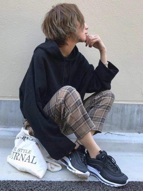 チェックパンツに黒スニーカーを履いた女性
