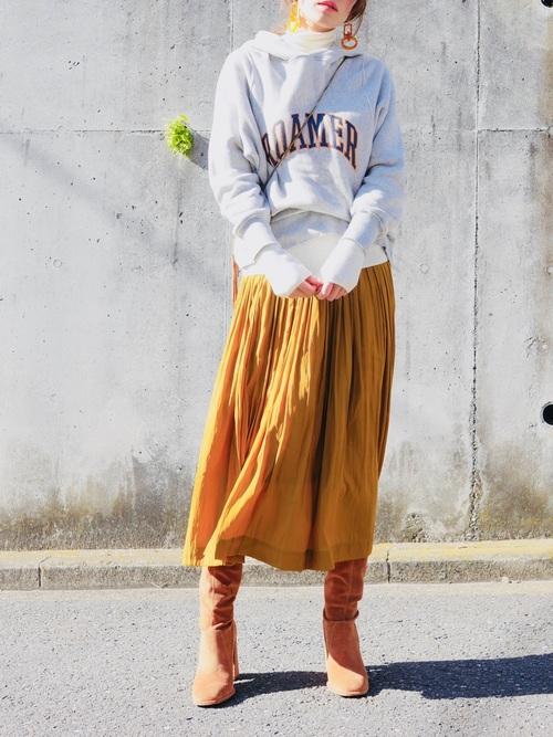 グレーのスウェットパーカーに白の薄手タートルニットを仕込んで、キャメルのスカートを合わせた女性