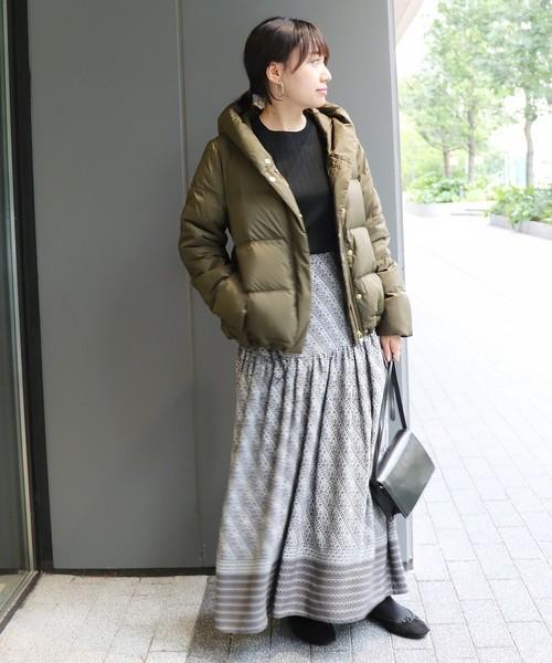 カーキのダウンコートに柄ロングスカートと黒バッグの秋の最高きおん11度の日にぴったりなレディースの服装
