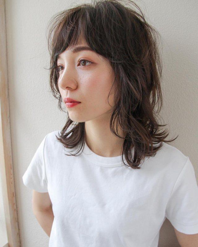 前髪を流したミディアムヘアの髪型をウルフカットでパーマにした丸顔女性の画像