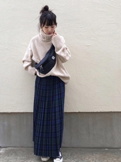 ベージュのタートルネックニットに青ベースのチェック柄スカートを合わせた女性