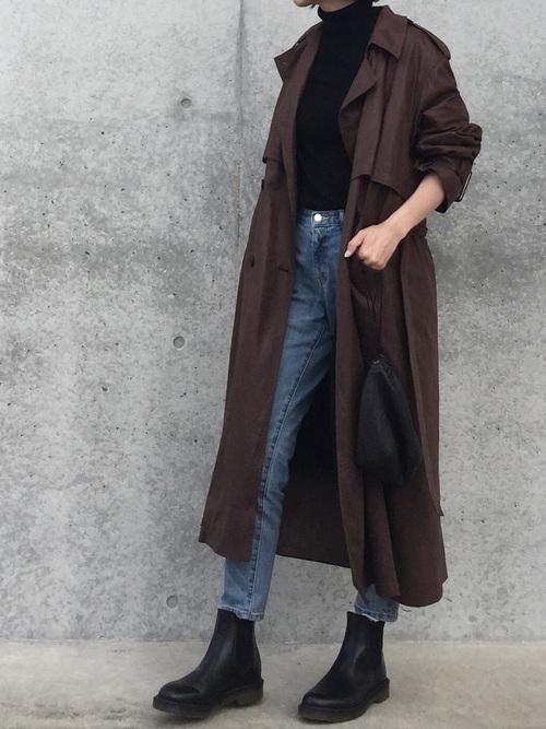 ブラウンのトレンチコートに黒のタートルネックニットとデニムパンツの秋の最低気温12度の日にぴったりなレディースの服装