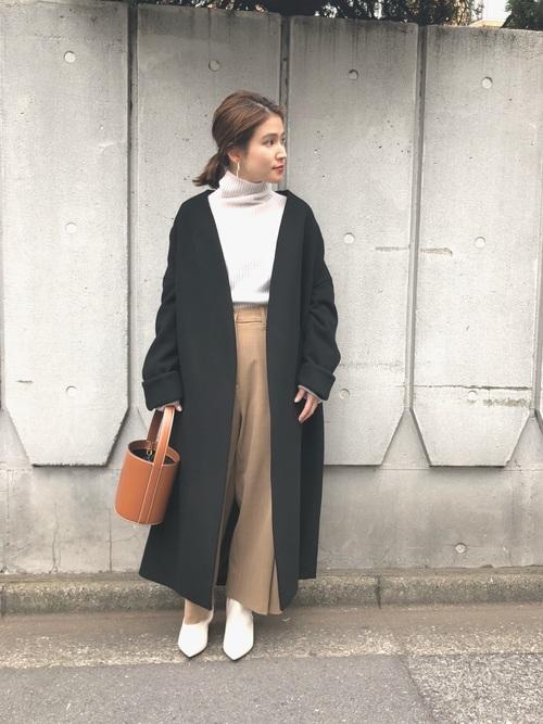 黒のコートにベージュパンツ、白のブーツにバケツバッグを合わせたコーデ