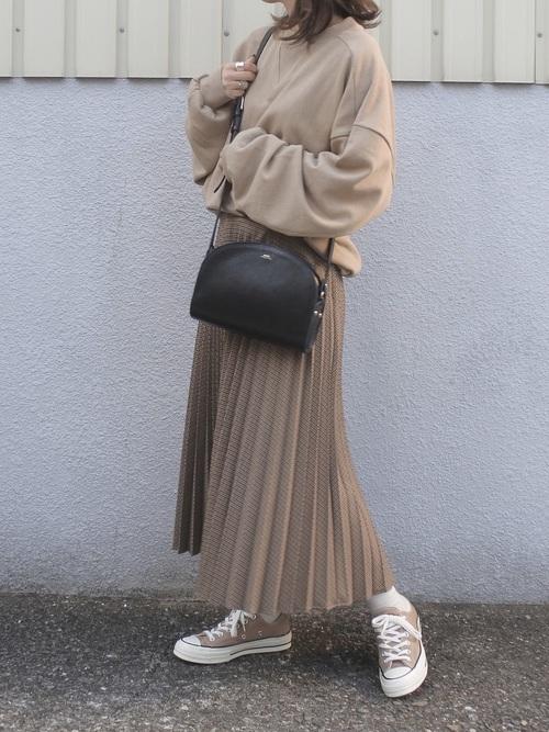 ベージュスウェットにベージュのプリーツスカート、ハーフムーンバッグを合わせたコーデ
