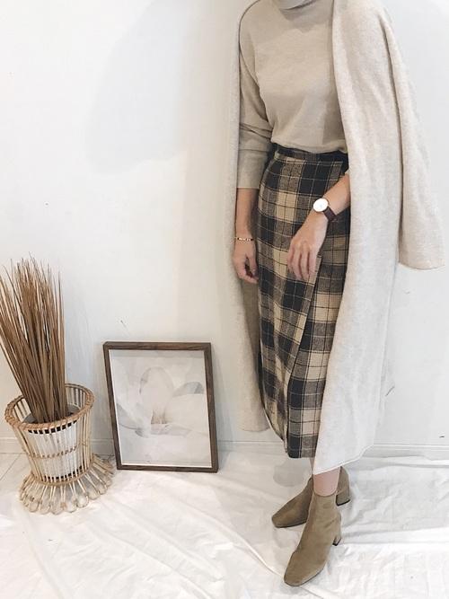 チェック柄スカートにベージュタートルネックニットの20代30代の女性におすすめな新年会の服装