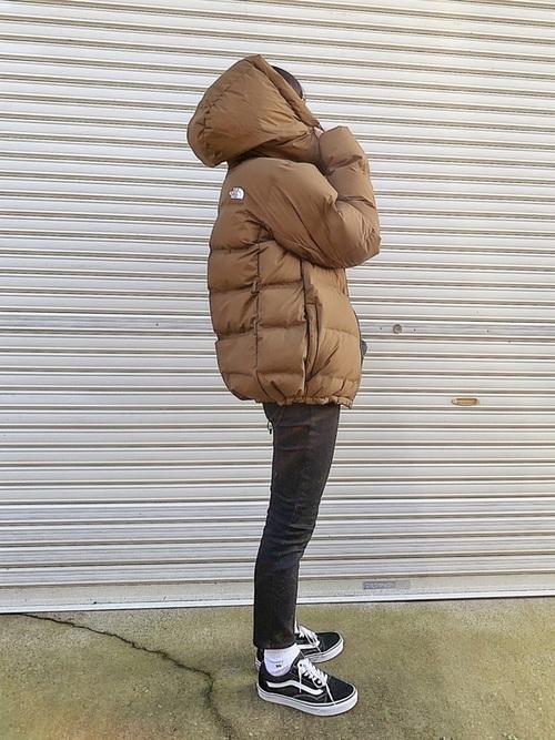 ブラウンのノースフェイスのダウンジャケットに黒スニーカーの冬の日にぴったりな女性の服装