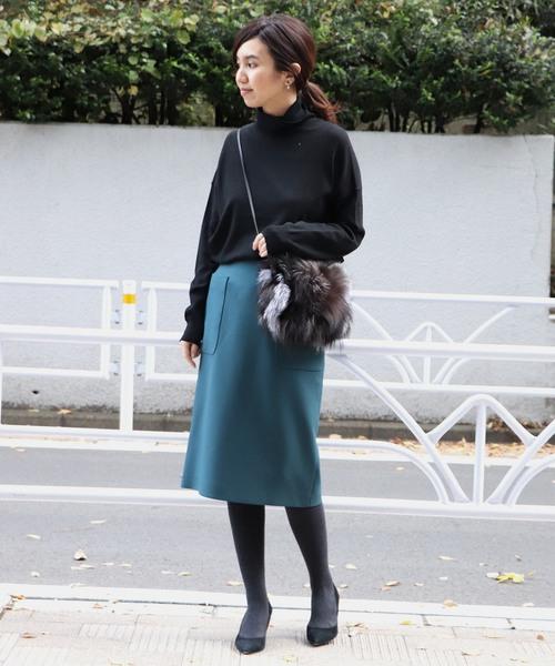 黒のニットにブルーのスカートを合わせて、グレーのタイツに黒のパンプスを合わせた女性
