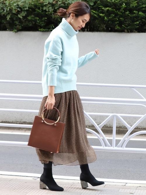 ブルーのタートルネックニットにブラウンのシルクスカートを合わせて、黒のタイツとマットな質感のショートブーツを合わせた女性