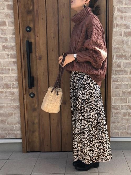 ブラウンのオフタートルケーブルニットにレオパード柄のスカートを合わせた女性