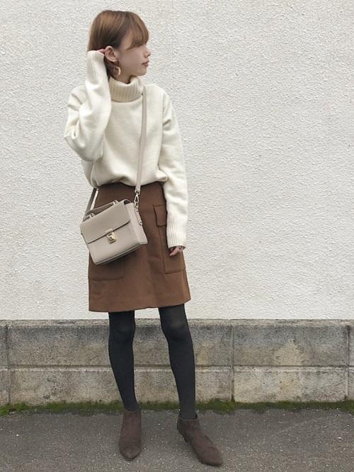 白のタートルネックニットにブラウンミニスカートの秋冬のおうちデートにぴったりな女性の服装