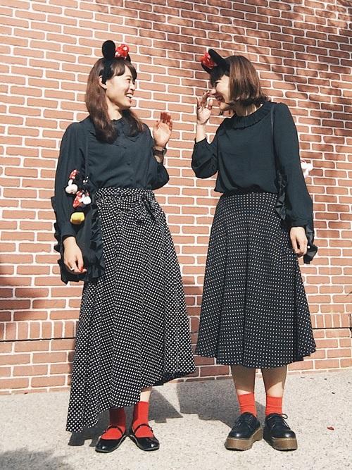 おそろいの黒ドット柄スカートに黒トップスと赤靴下を合わせた大人女子の冬ディズニーコーディネート