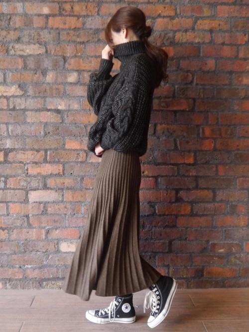 黒のざっくりニットにブラウンのニットプリーツスカートを合わせた女性