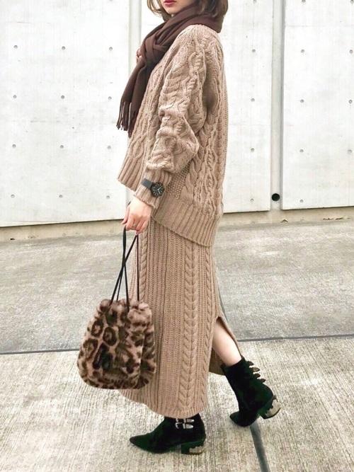 ブラウンのケーブル編みのニットセットアップを着た女性