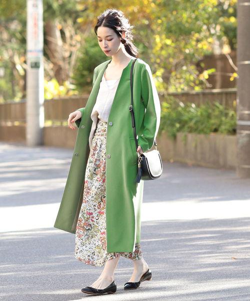 花柄スカートにグリーンコートを着た女性