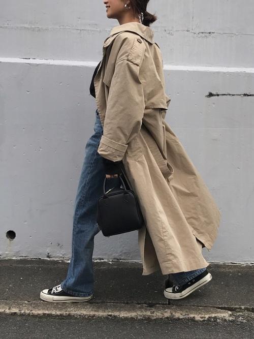 ベージュトレンチコートにデニムパンツとスニーカーの秋冬の最高気温16度の日にぴったりなレディースの服装