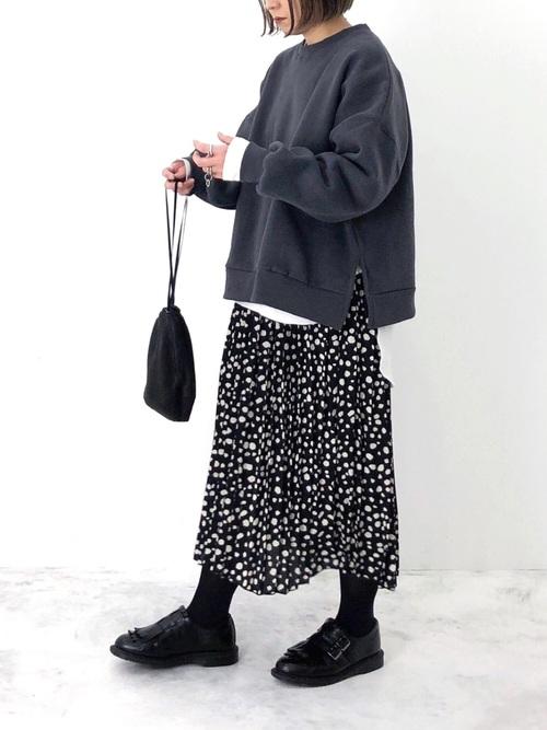 黒スウェットに黒スカートコーデの女性