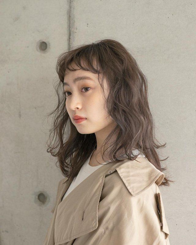 丸顔さんに似合う髪型の短い前髪にパーマロングヘアスタイルにした女性の画像
