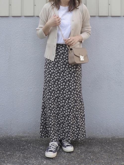 小花柄スカートに白カーデコーデの女性