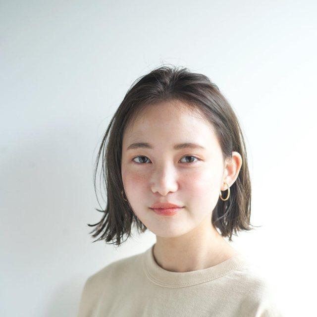 丸顔さんに似合う髪型の前髪ありの黒髪外ハネストレートボブヘアスタイルにした女性の画像
